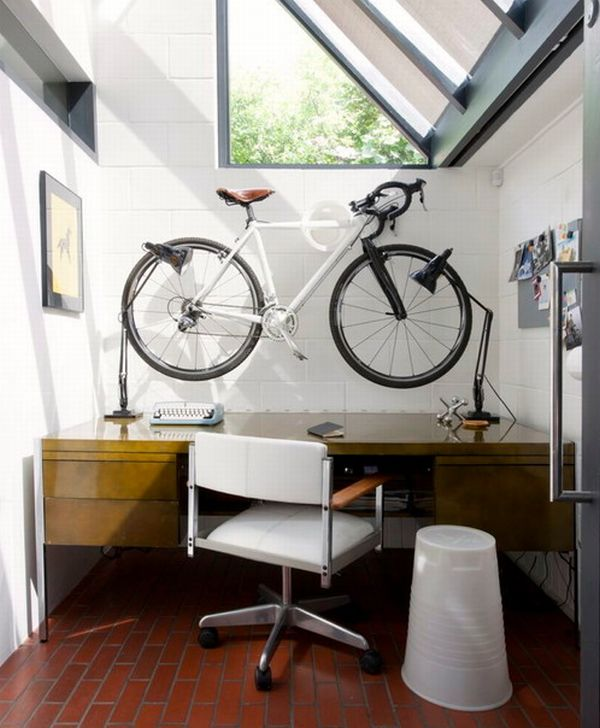 Space-conscious-home-office-with-sloped-windows-and-a-bicycle-mounted-on-the-wall